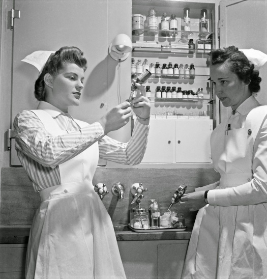 Nurse training. A graduate nurse (right) watches student Susan Petty prepare a hypodermic for a patient. Strict adherence to doctors' orders is something every probationer must learn, 19